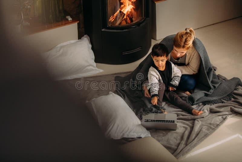 母亲和儿子有膝上型计算机的在壁炉附近 库存图片