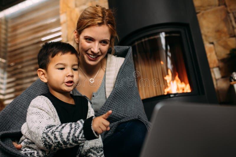 母亲和儿子有膝上型计算机的在家 库存照片