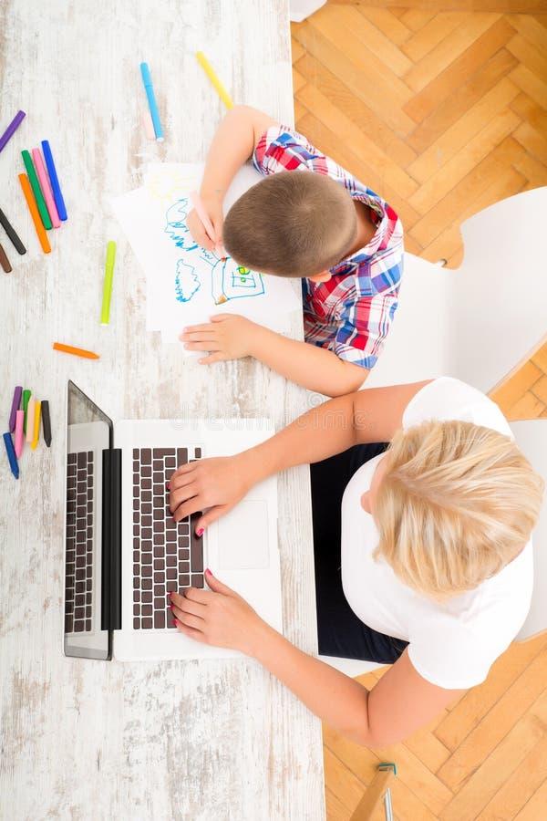 母亲和儿子有膝上型计算机的在家 库存图片