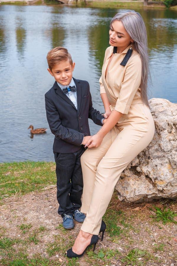 母亲和儿子步行在湖的公园 库存照片