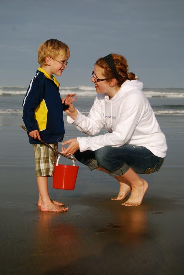 母亲和儿子海滩的与红色桶 库存图片