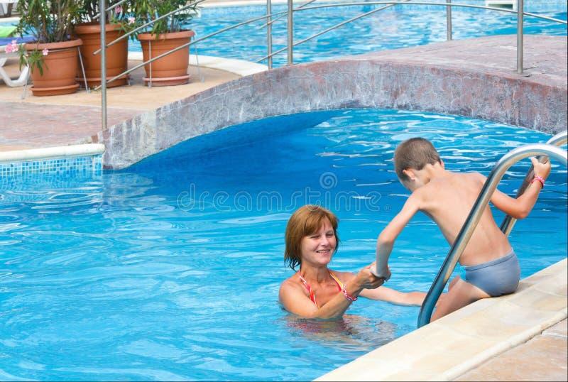 母亲和儿子游泳池的。 库存图片