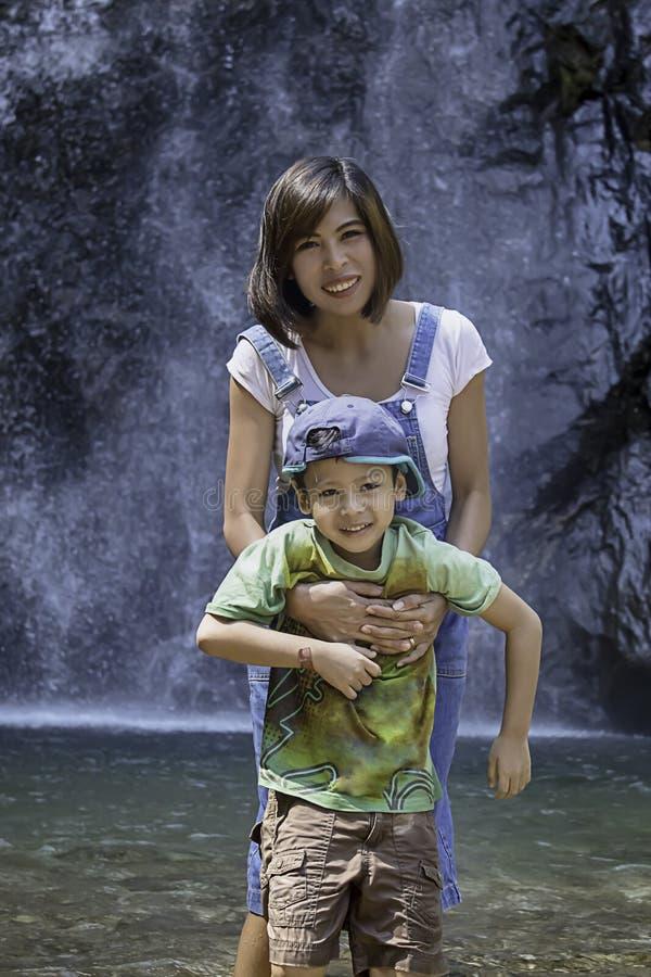 母亲和儿子演奏水在Chok Kra-DinÂ瀑布在北碧在泰国 免版税库存图片