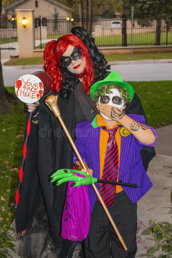 母亲和儿子站立在门的明亮的色的万圣夜服装的欺骗对待在邻里的r 免版税库存照片