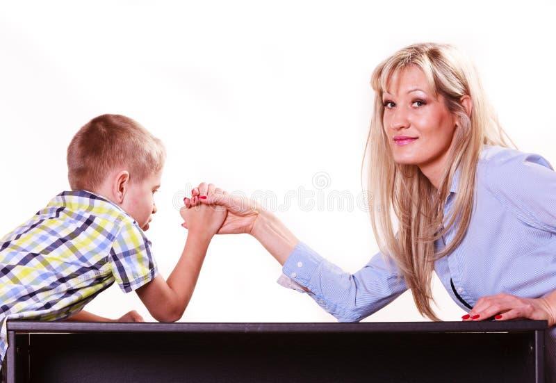 母亲和儿子胳膊格斗坐在桌上 库存照片