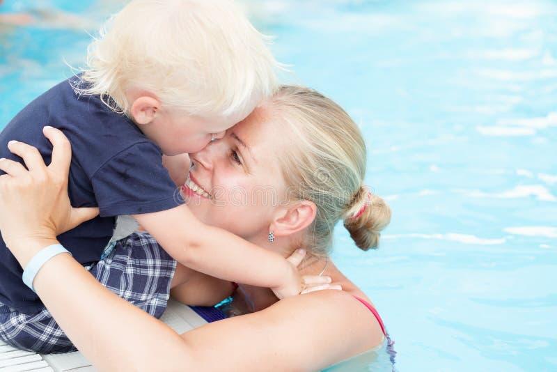 母亲和儿子获得乐趣由游泳池 免版税图库摄影