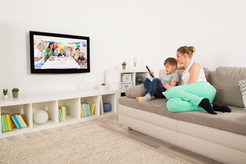 母亲和儿子观看的电视在家 免版税图库摄影