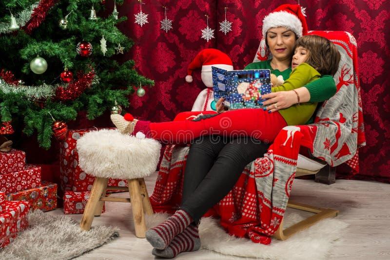 母亲和儿子读书一起圣诞节书 免版税图库摄影
