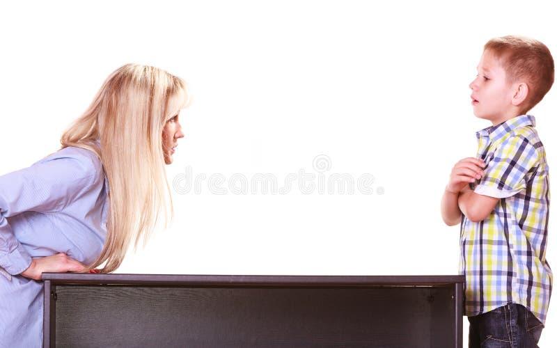 母亲和儿子谈话并且争论坐在桌上 免版税库存图片
