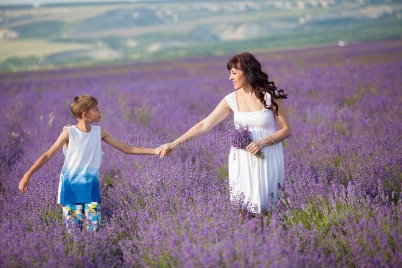 母亲和儿子紫色淡紫色领域 免版税图库摄影