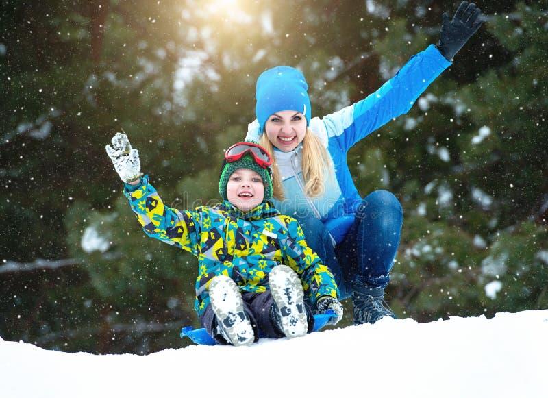 母亲和儿子sledding在一个多雪的森林里 冬天乐趣为家庭圣诞节假期 免版税图库摄影