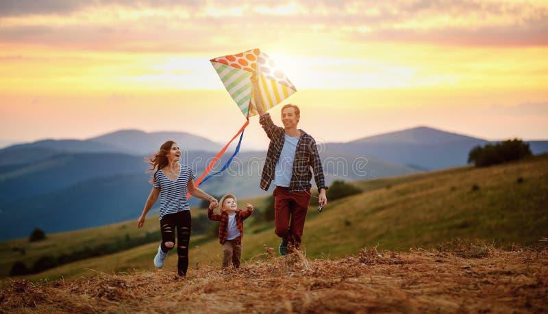 母亲和儿童儿子发射的幸福家庭父亲在自然的一只风筝在日落 免版税库存照片