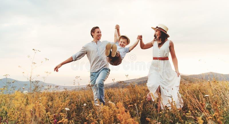 母亲和儿童儿子的幸福家庭父亲自然日落的 免版税库存图片
