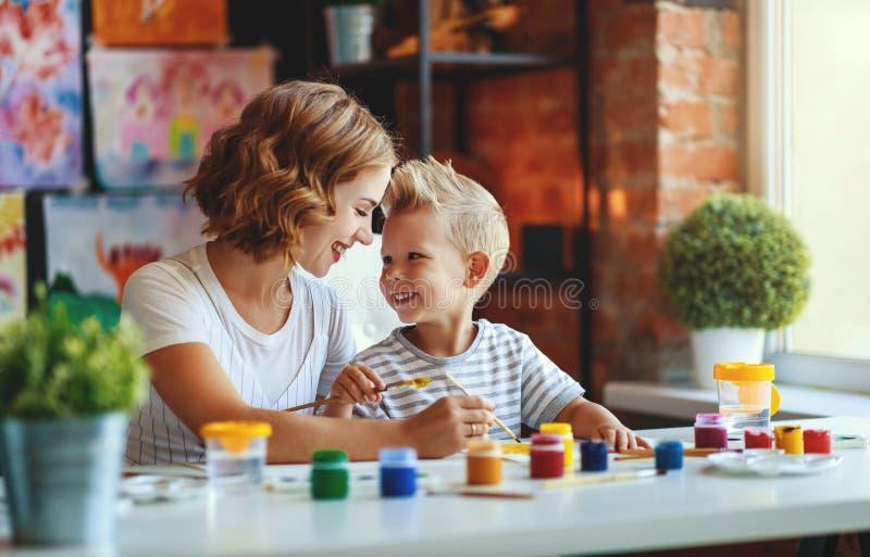 母亲和儿童儿子绘画在创造性画在幼儿园 图库摄影