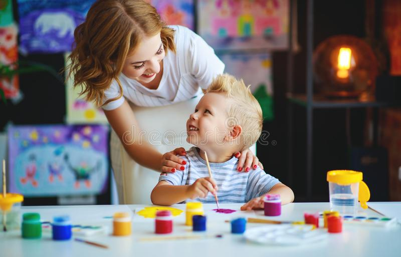 母亲和儿童儿子绘画在创造性画在幼儿园 免版税图库摄影
