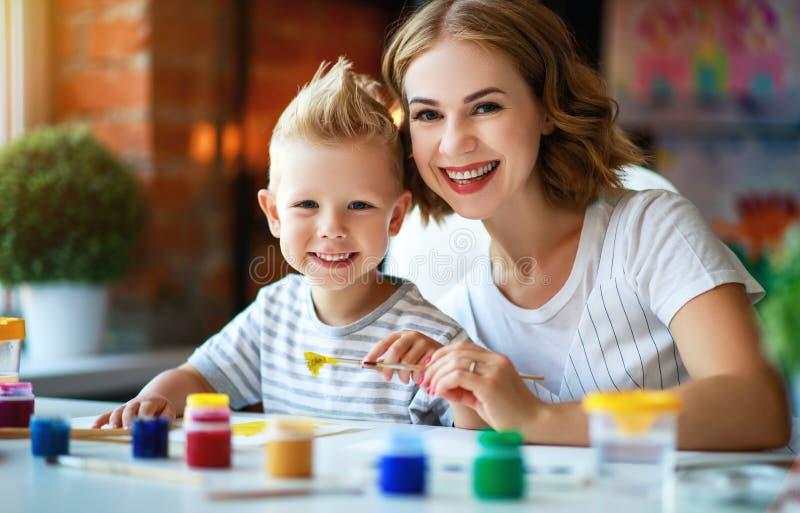 母亲和儿童儿子绘画在创造性画在幼儿园 母亲和儿童儿子绘画画参与创造性 免版税库存图片