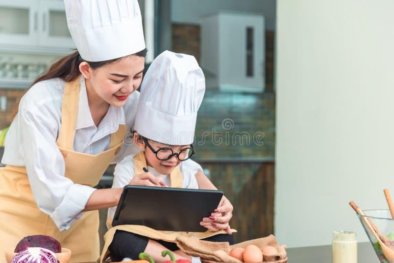 母亲和儿童和计算机用途,发明了食物菜单 图库摄影