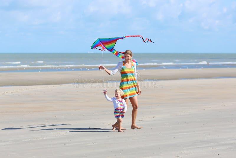 母亲和儿童在海滩的飞行风筝 免版税库存照片