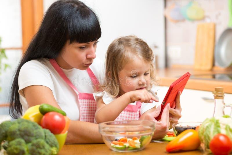 母亲和儿童女儿在厨房里准备食谱 图库摄影