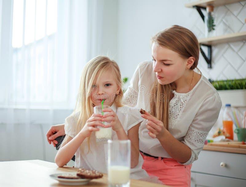 母亲和儿童女儿在食用家庭的厨房里乐趣饮用奶,健康家庭生活方式 免版税库存图片