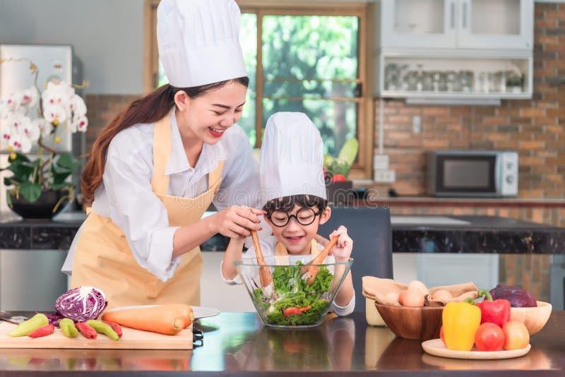 母亲和儿童女儿女孩烹调沙拉并且在厨房里获得乐趣 自创食物和小的帮手 免版税库存图片