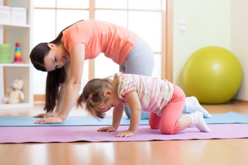 母亲和儿童女儿实践的瑜伽一起在家 体育和家庭观念 库存照片