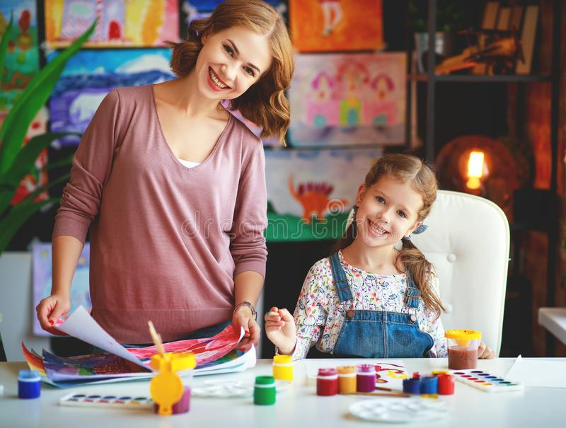 母亲和儿童女儿绘画在创造性画在幼儿园 免版税库存图片