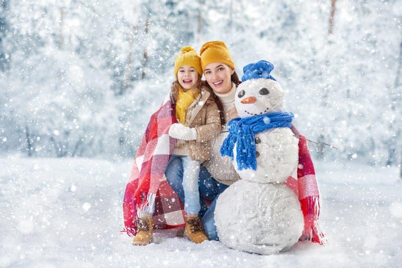 母亲和儿童女孩在一个冬天走 免版税库存图片