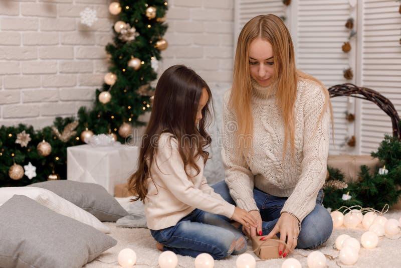 母亲和儿童女孩组装圣诞礼物在家 图库摄影