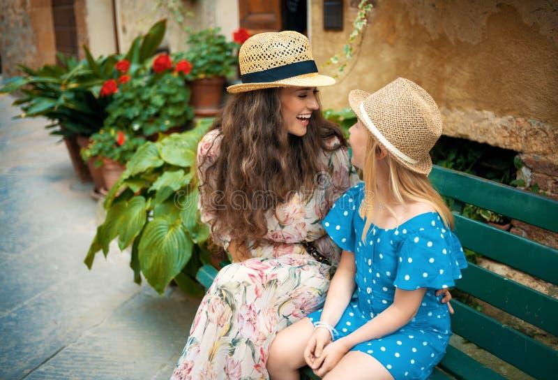 母亲和儿童旅行家在皮恩扎,坐在长凳的意大利 免版税图库摄影