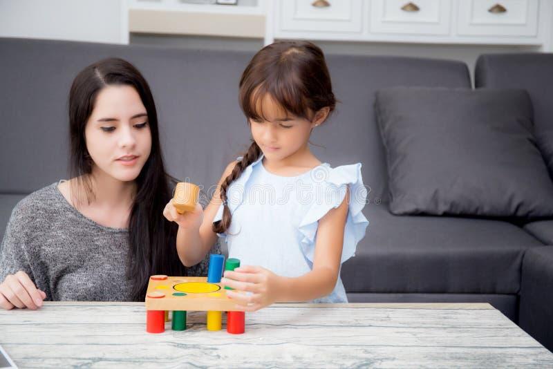 母亲和儿童游戏在客厅在家一起戏弄, k 免版税库存照片