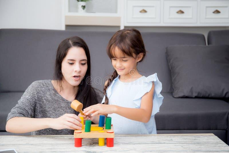 母亲和儿童游戏在客厅在家一起戏弄, k 免版税库存图片