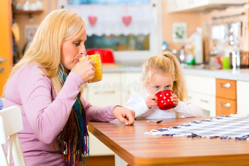 母亲和儿童饮用奶在厨房里 库存图片