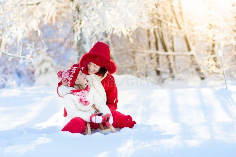 母亲和儿童sledding 冬天雪乐趣 在雪橇的家庭 免版税库存图片