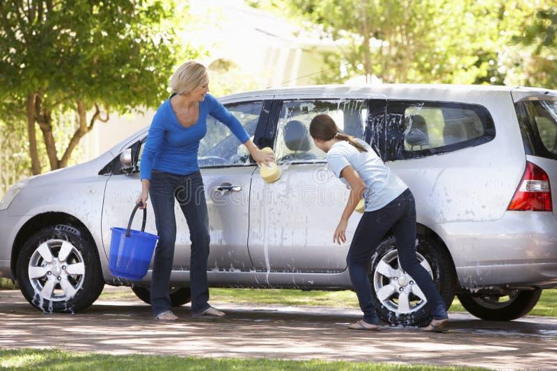 母亲和十几岁的女儿洗涤的汽车一起 免版税图库摄影