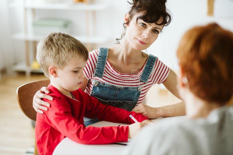 母亲和和小男孩红色毛线衣的通过画学会在ADHD疗法期间 免版税库存照片