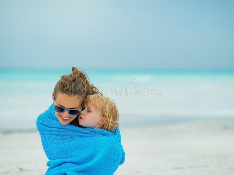 母亲和在海滩的毛巾包裹的女婴 免版税库存图片