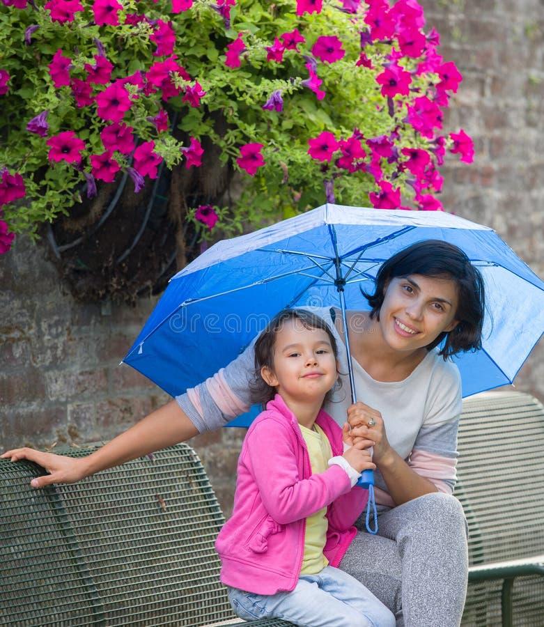 母亲和女儿一条长凳的与伞 免版税库存图片