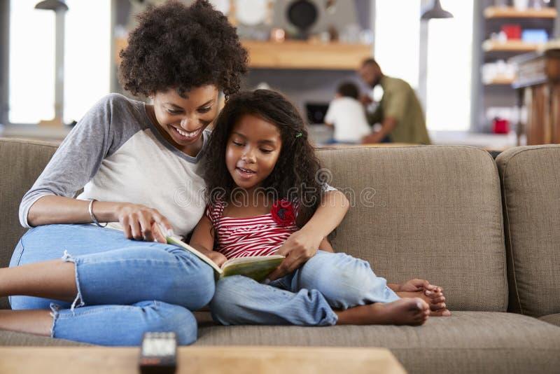 母亲和女儿一起坐在休息室阅读书的沙发 库存照片