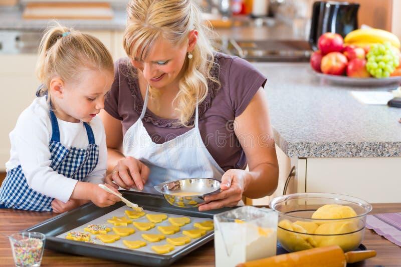 母亲和女儿一起烘烤曲奇饼 图库摄影