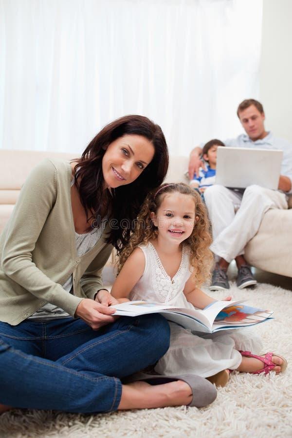 母亲和女儿一起阅读书 库存图片