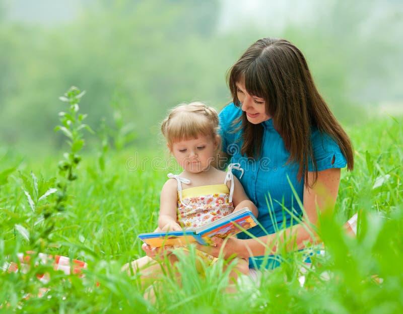 母亲和女儿一起阅读书 免版税库存照片