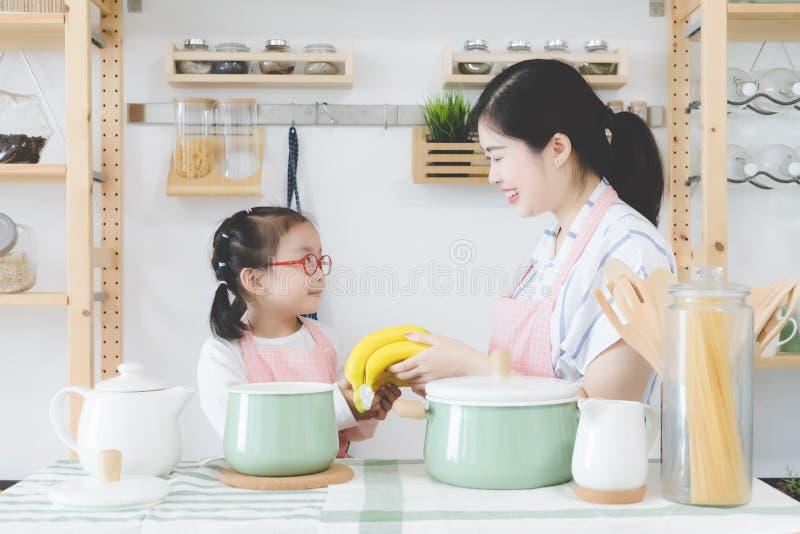 母亲和女儿与一笑容一起烹调在现代木厨房里,有厨房用具和烹调的 库存照片
