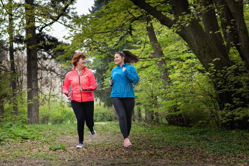 母亲和女儿佩带的运动服和赛跑在森林里 免版税图库摄影