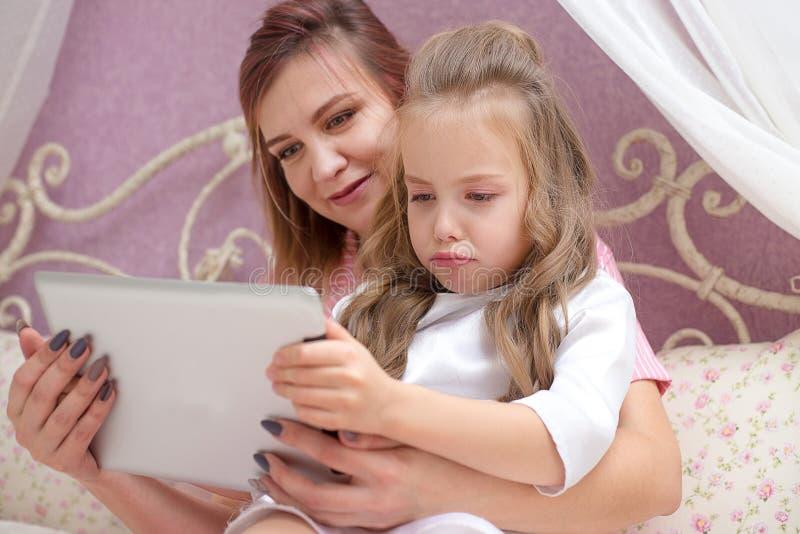 母亲和女儿使用一台片剂计算机 免版税图库摄影