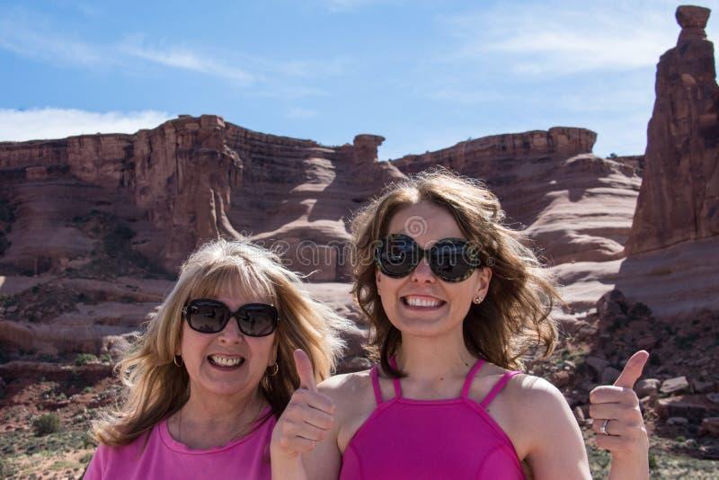 母亲和女儿假期旅客在穿桃红色衣物的拱门国家公园 免版税库存图片