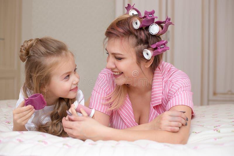 母亲和女儿做着头发并且获得乐趣 免版税库存图片