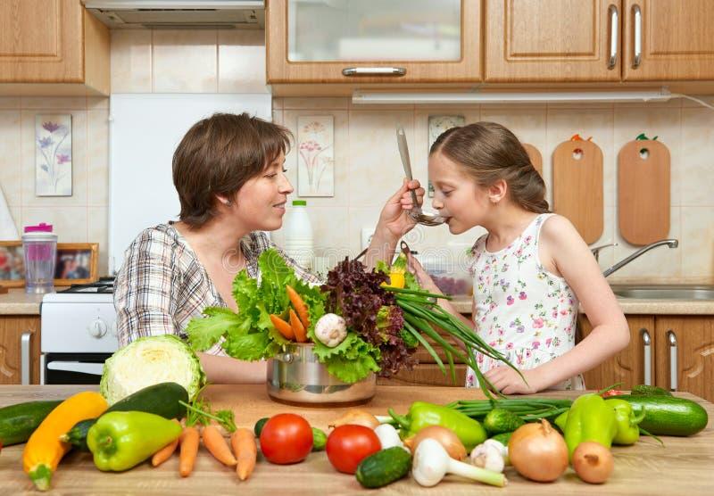 母亲和女儿厨师和口味汤从菜 家庭厨房内部 父母和孩子、妇女和女孩 健康食物骗局 库存图片