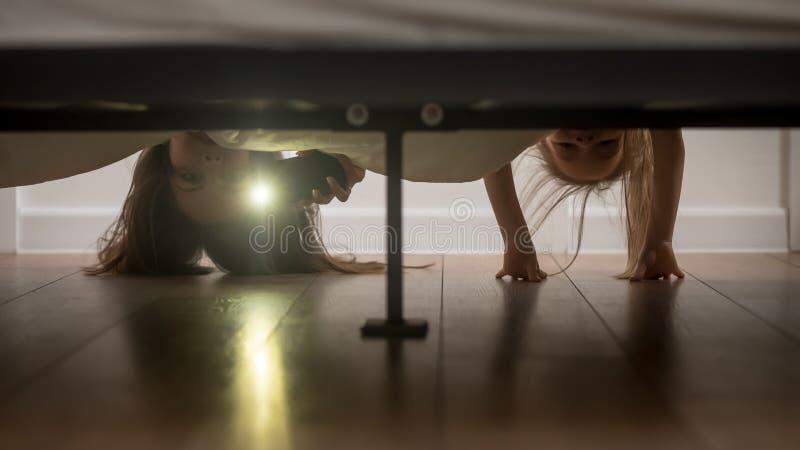 母亲和女儿发光看在床下的手电 免版税图库摄影