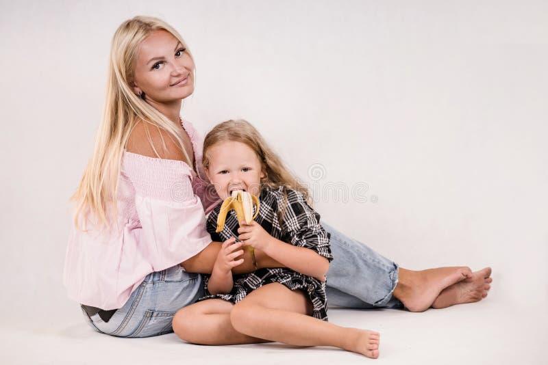母亲和女儿吃着在白色背景的香蕉 库存图片
